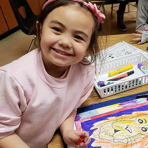 Smiling child drawing a lion